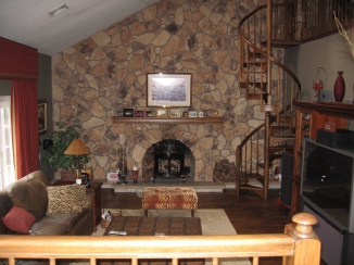 Family room with stone wall, fireplace and three skylights and soaring ceilings. Entrance to garage.
